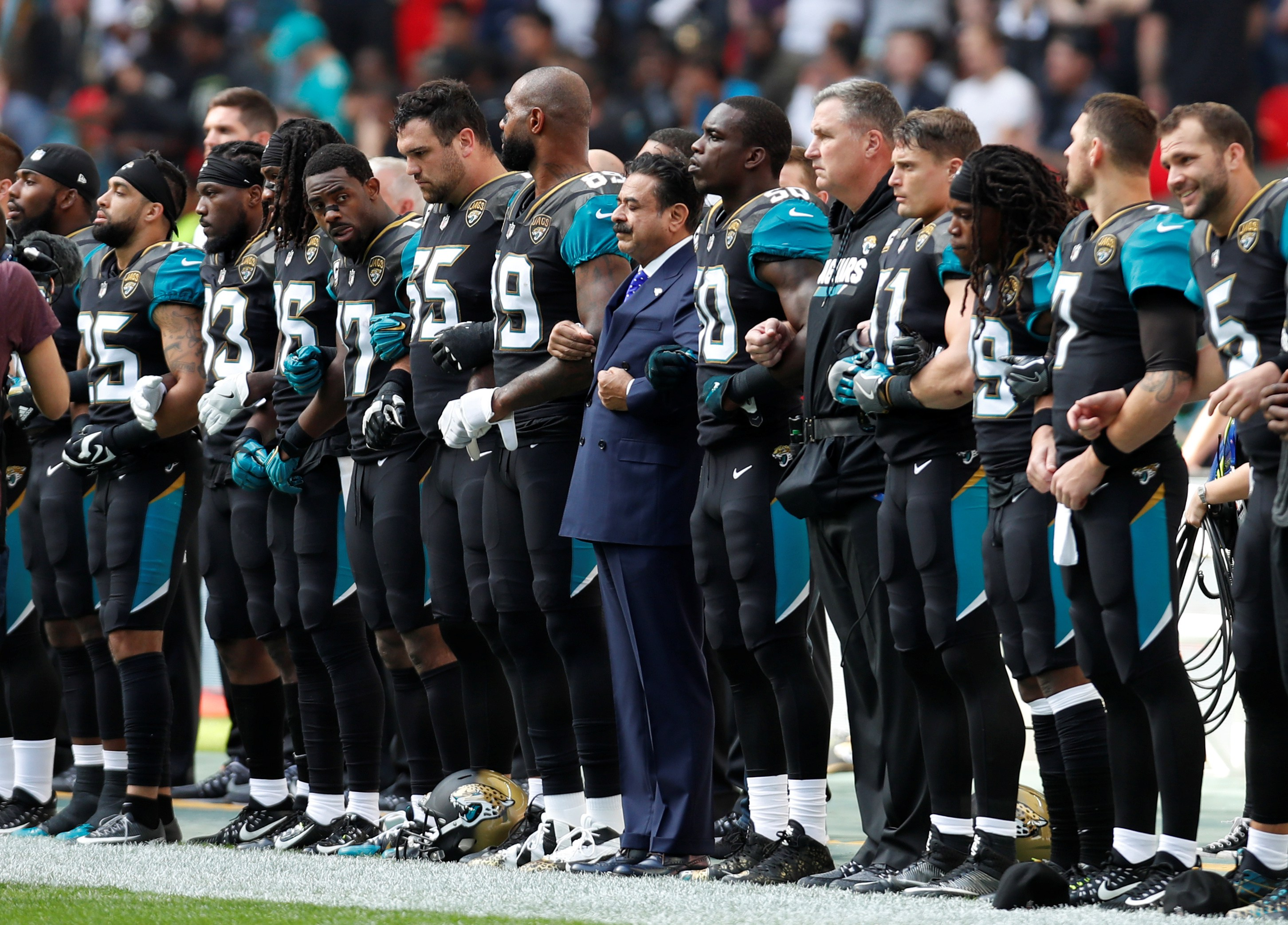 NFL Football - Jacksonville Jaguars vs Baltimore Ravens - NFL International Series - Wembley Stadium, London, Britain - September 24, 2017 Jacksonville Jaguars owner Shahid Khan links arms with players during the national anthems before the match Action Images via Reuters/Paul Childs - RC172380A0B0